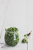 Green kale pesto in a jar and on a spoon