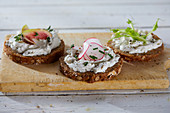 Wholemeal bread topped with herb cream cheese, vegetables and herbs (vegan)