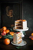Blood orange cake with caramel sauce on a cake stand, sliced