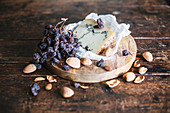 Blue cheese, dried grapes and almonds on a wooden plate