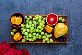 Selection of colorful organic fruit on rustic wooden chopping board over slate background