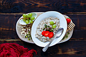 Close up of Homemade oatmeal porridge with berries and seeds in bowl on dark rustic background