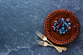 Close up of delicious homemade chocolate cake with blueberries and blackberries on vintage table