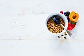 White breakfast bowl of tasty homemade granola, fresh berries and fruits on rustic background