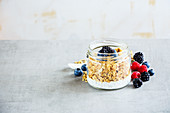 Tasty breakfast in jar, Greek yogurt, granola, fresh berry breakfast, white wooden wall background