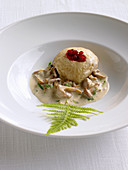 A steamed spelt dumpling with mushroom sauce and cranberry jam