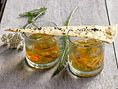 Clear vegetable soup with yarrow in glasses