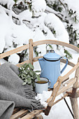 A tin jug and a cup of tea on a wooden sledge in the snow