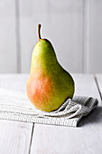 A green and red pear on a cloth napkin