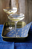 Two champagne glasses with gold rims on a gold tray, and a paper napkin decorated with the words 'let's eat & dance'
