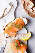 Two slices of bread with cream cheese, salmon and dill on a wooden board