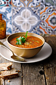 Spicy carrot soup with coriander and bread in an oriental setting