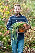 Mann bringt Korb mit frisch geerntetem Gemüse