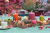 Herbstliche Tischdekoration mit Kerzen, Äpfeln und Hagebutten