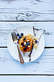 Plate of delicious blueberries homemade pancakes with honey and almonds for breakfast on rustic wooden white plywood background