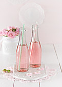 Two bottles of pink prosecco with straws