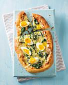 Amerikanische Pizza mit Spinat und gekochtem Ei
