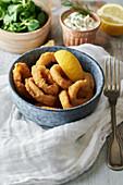 Frittierte Tintenfischringe mit Zitronenspalte in Keramikschale