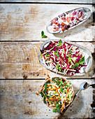 Drei Kohlsalate: mit Senf und Speck, mit Apfel, Rote Bete und Pfefferminze und asiatischer Kohlsalat mit gebratenen Erdnüssen