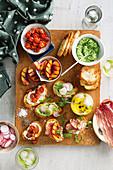 Verschiedene Bruschetta mit Ziegenkäse und karamellisierten Tomaten, Erbsenpüree und Radieschen
