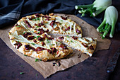 A pizza with fennel, dried tomatoes and smoked tofu (vegan)