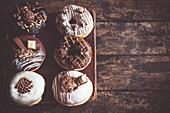 Braun und weiss glasierte Donuts auf Holzuntergrund