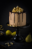 Pear and nougat pie with caramel popcorn on a black cake stand