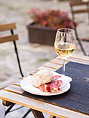 A ham sandwich and a glass of white wine on a bistro table outdoors