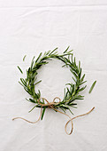 A wreath of rosemary sprigs against a white background
