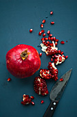 A whole pomegranate and pomegranate pieces with a knife on a blue background