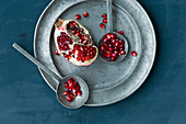 Pomegranate pieces and seeds on a pewter plate with two metal spoons (top view)