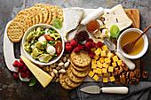 A cheese plate with tortellini salad, crackers, fruit and nuts