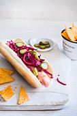 A hot dog with pickled red cabbage and gherkins