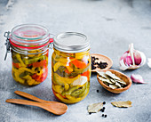 Pickled peppers in preserving jars with various ingredients