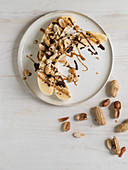 Halved bananas with peanuts, peanut butter and chocolate