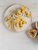Halved bananas with mango, passion fruit and coconut