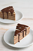 Two pieces of Mille Crepes cake (pancake cake) with chocolate