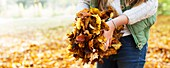 Girl holding a pile of Autumn leaves