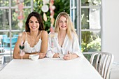 Women sitting at table with coffee, smiling