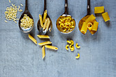 Mix of italian pasta in old metal spoons over vintage background