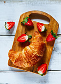 Fresh croissant and ripe berries on vintage rustic chopping board over white wooden background