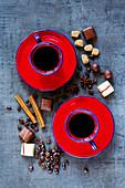 Kaffeetassen mit roten Untertassen, Gewürzen und Schokolade auf grauem Untergrund