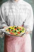 Frau hält vegetarische Gemüse-Quiche (Low Carb)