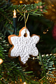 Gingerbread snowflake cookie hanging on a christmas tree