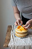 Geschichteten Orangenkuchen mit Orangenscheiben dekorieren