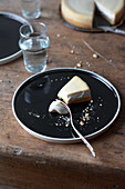 A piece of vegan New York cheesecake on a black plate