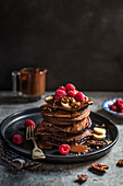 Chocolate pancakes with chocolate sauce, sliced bananas ad raspberries