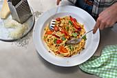 Spaghetti mit Chili, Basilikum und Tomaten mischen