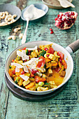 Fried tofu curry with broccoli, coconut chips and pomegranate seeds