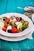 Griechischer Salat in weißem Teller auf türkisfarbenem Tisch